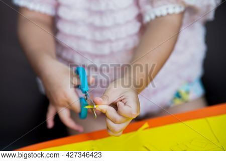 Closeup Shot Of A Child's Hand Using Blue Scissors To Carefully Cut A Small Piece Of Yellow Colored