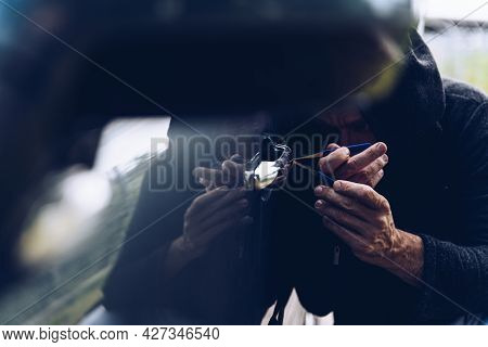 The Thief Opening A Car Door With A Lockpick.
