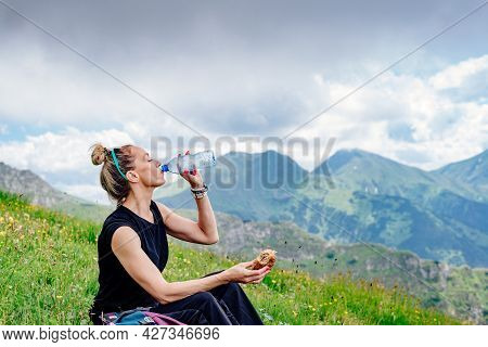 Hiker Woman Sitting, Drinking Water And Eating Sandwich, Resting On The Grass In The Mountains.