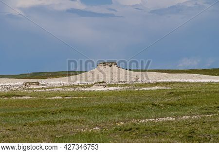 Badlands National Park, Sd, Usa - June 1, 2008: Patch Of Green Grass On Top Of Small Hill Composed O