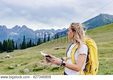 Adventurous Woman Navigating In With A Topographic Map In The Beautiful Polish Mountains.