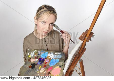 Young Artist Poses With A Palette And Brush In Front Of An Easel In The Studio On A White Background