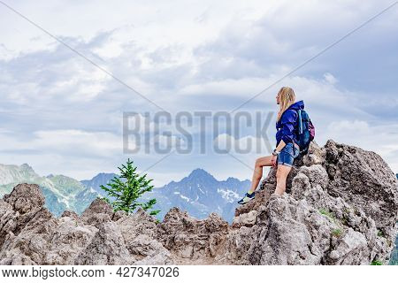 A Blonde Tourist Is Sitting On A Rock In The Beautiful Polish Mountains.