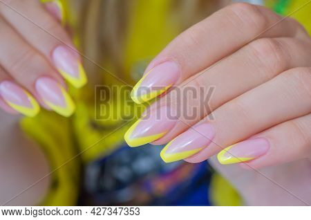 The Hand Of A Young Woman With A French Manicure Of Yellow Color, Nails In The Shape Of A Ballerina.