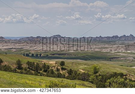 Badlands National Park, Sd, Usa - June 1, 2008: Green Landscape With Dark Trees In Crevasses And Lar