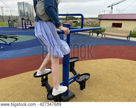 A Woman Goes In For Sports On A New Modern Blue Fitness Leg Trainer For Walking And Running On An Ou