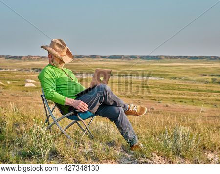 Senior man in cowboy hat is taking a nap in a folding chair while working on laptop in the middle of nowhere, early morning in Pawnee National Grassland in Colorado
