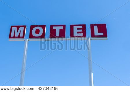 Generic Sign For A Motel Against Blue Sky. Red And White Lettering