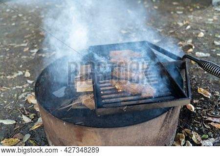 Marinated Chicken Breasts Cooking Over A Campfire Ring. Lots Of Smoke From The Campfire. Selective F