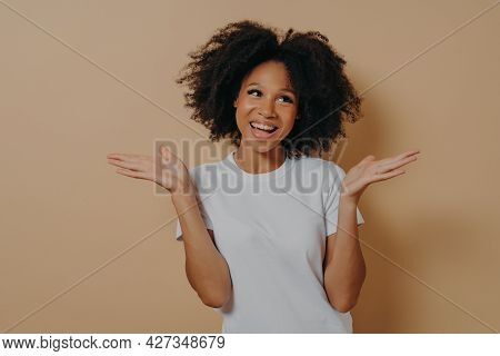 Young Smiling Mixed Race Curly Woman Raising Both Hands With Hesitation And Looking Aside, Making De