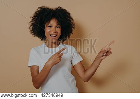 Young African American Girl Wearing Casual Clothes Cheerfully And Broadly Smiling While Pointing Wit