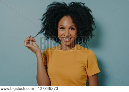 Studio Portrait Of Beautiful Young Dark Skinned Woman With Shaggy Hairstyle Smiling Cheerfully, Show