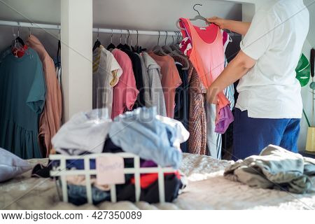 A Woman Selecting Clothes From Her Wardrobe For Donating To A Charity Shop. Decluttering Clothes, So