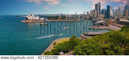 SYDNEY, NEW SOUTH WALES, AUSTRALIA - OCTOBER 21, 2013: Sunset over Sydney downtown and Circular quay seen from above. The famous Sydney Opera House could be seen on the left. Panoramic photo