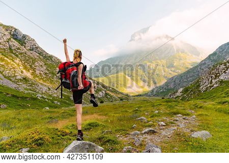 Caucasian And Young Person With His Back Turned, With A Backpack And On Top Of A Rock Lifting One Le