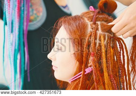 Cool Hairstyle Made Of Artificial Hair. Barber Braids Dreadlocks. Hairdresser Weaves Braids With Kan