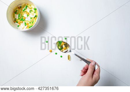 Vitamins And Tablets Are Served In A Plate On A White Wooden Table. A Womans Hand Holds A Spoon With