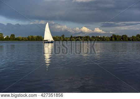 A Yacht Sailing Under White Sails On Calm Blue Water Against A Background Of Blue Sky With Clouds An