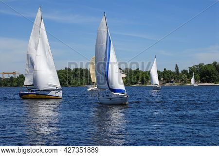 Racing Yachts In The Sea On Blue Sky Background. Beautiful Blue Sky Over Calm Sea With Sunlight Refl