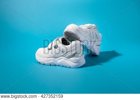 Side View Of A Balanced Composition Of Two White Kid Sneakers With Velcro On A Blue Paper Background