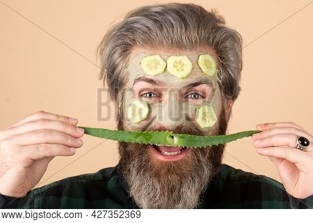 Funny Male Model With Clay Mask And Cucumber Slices, Aloe Vera Moustache On Face. Spa, Dermatology,