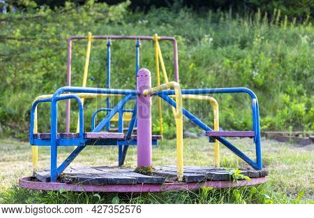 Abandoned Playground. Rusty Non-working Carousel. Childrens Games.