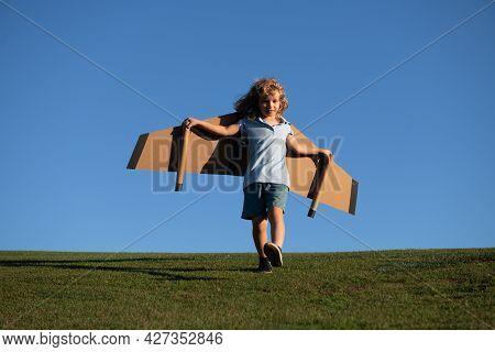 Cute Dreamer Boy Playing With A Cardboard Airplane On Sky. Childhood. Fantasy, Imagination.