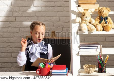 Serious Funny School Girl Reading Book In Classroom At School. Kid Studying At School. Schoolchild D