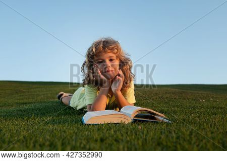 Kid Reading Book Laying On Grass On Grass And Sky Background With Copy Space. Schoolboy With A Book