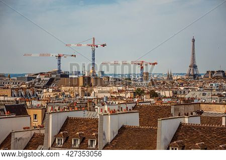 Close-up Of Buildings Rooftops, Cranes And Eiffel Tower On The Horizon In Paris. One Of The Most Imp
