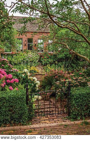 Charming Brick Rustic House With Flowered Garden, Leafy Trees And Iron Gate In A Cloudy Day At Drimm