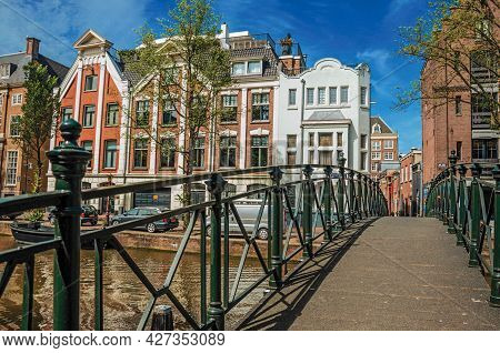 Amsterdam, Netherlands - June 27, 2017. Footbridge With Iron Banister On Tree-lined Canal, Old Build