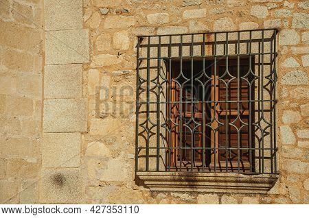 Wooden Window With Wrought Iron Grid On The Stone Facade Of Gothic Building, In A Sunny Day At Cacer