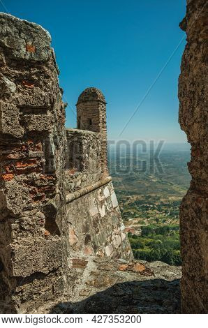 Stone Wall And Watchtower Over Cliff With Hilly Landscape Seen By Crenel In The Marvao Castle. An Am