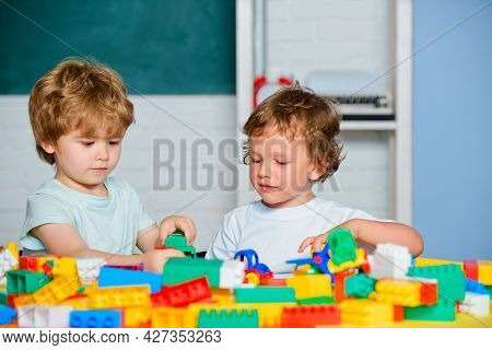 Happy Cute Clever Boy Pupils. Toddler Children Friends Play With Blocks, Trains And Cars. Educationa
