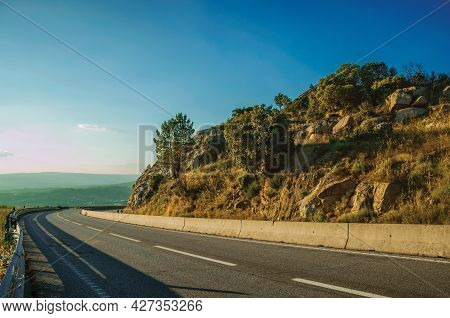 Country Road Passing On Hilly Landscape With Rocks On Sunset At The Highlands Of Serra Da Estrela. T