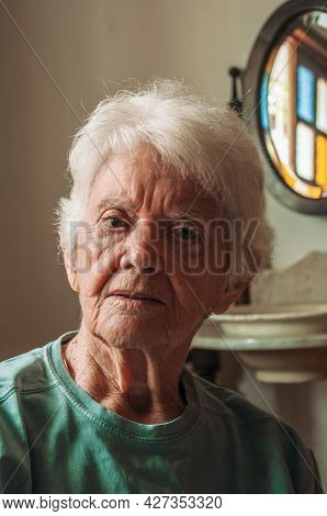 Portrait Of Old Lady With White Hair Inside Her House In Sao Paulo. The Gigantic City, Famous For It