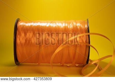 An Orange Reel Of Tape In Horizontal Position.