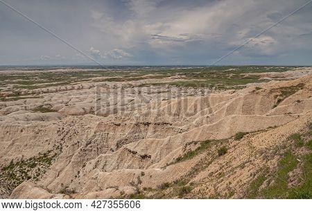 Badlands National Park, Sd, Usa - June 1, 2008: Bad Weather Cloudscape Approacing Over Beige Geologi