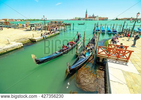 Venice, Italy - May 9, 2021: Traditional Gondola Boats With Tourists In Tour On Canal Of Giudecca By