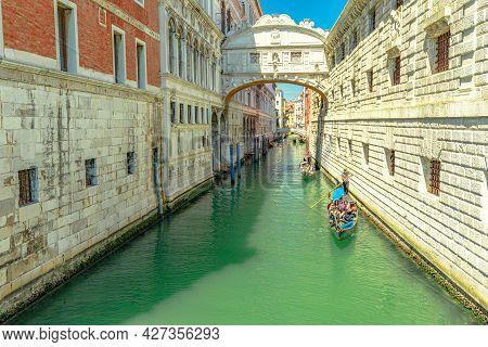 Venice, Italy - May 9, 2021: Romantic Gondola Touristic Cruise Under The Sospiri Arcade Bridge Leadi