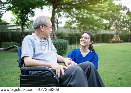 Caucasian Caregiver Doctor Talk With Older Disabled Man On Wheelchair. Attractive Nurse Taking Care