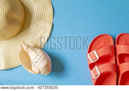 Summer Seaside Holiday Concept - Hat, Shell And Slippers On Blue Background