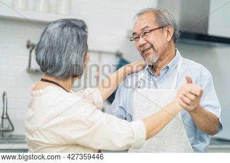 Asian Romance Senior Elderly Couple Stay At Home Enjoy Cook In Kitchen. Happy Grandfather Hug Grandm
