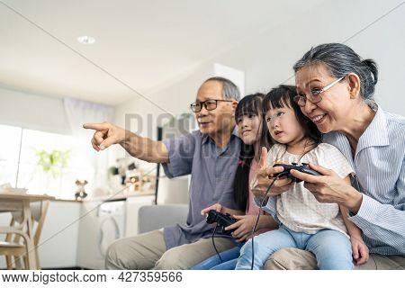 Asian Happy Family Stay Home Grandparent Play Game With Little Girl. Loving Senior Elder Older Coupl