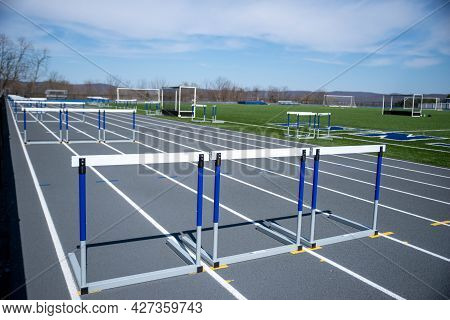 No People, Just An Empty Athletic Track With Hurdles Ready For A Track And Field Race, Green Grass,