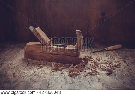 Plane jointer carpenter or joiner tool and wooden shavings. Woodworking tools on wooden table. Carpentry workshop