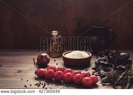 Food ingredients for pizza cooking and tomato with spice for homemade bread baking on table. Recipe concept spice and herb at wooden tabletop background. Bakery concept in kitchen