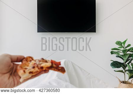 Person On Bed And Eating Pizza Watch Television. Concept Of Stay Home.