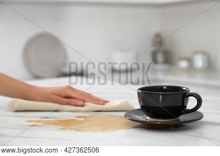 Woman Cleaning Spilled Coffee On White Marble Table In Kitchen, Closeup. Space For Text